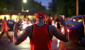 "FERGUSON, MO - AUGUST 15: Demonstrators gather along West Florissant Avenue to protest the shooting of Michael Brown on August 15, 2014 in Ferguson, Missouri. Brown was shot and killed by a Ferguson police officer on August 9. Protestors raise their hands and chant ""Hands up, don't shoot"" as a rally cry to draw attention to reports that stated Brown's hands were raised when he was shot. Tonight demonstration again ended with protestors clashing with police followed by more looting. (Photo by Scott Olson/Getty Images)"