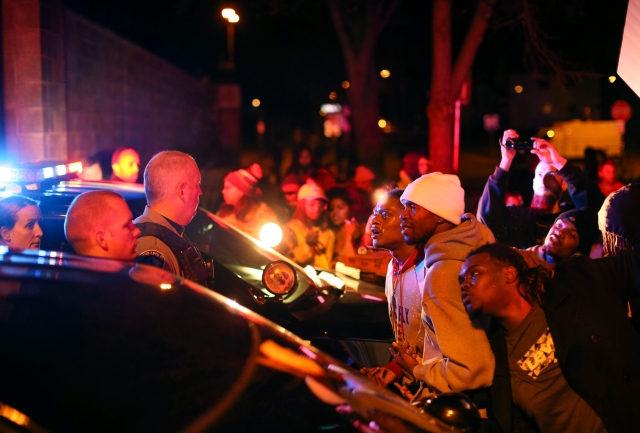 Demonstrators chanted at Minneapolis police officers at the side entrance to the 4th Precinct station on Morgan Ave. N. Sunday, Nov. 15, 2015, in Minneapolis, after a man was shot by Minneapolis police early Sunday morning, Black Lives Matters and others protested Sunday night. (Jeff Wheeler/Star Tribune via AP)